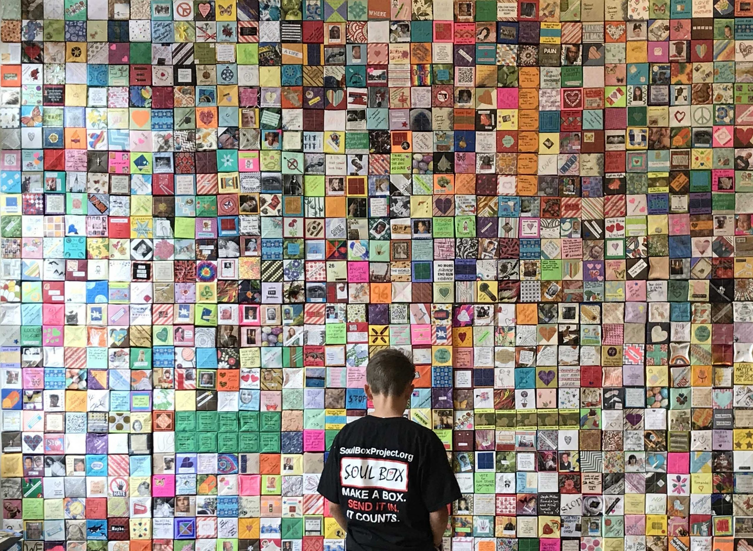 Boy views wall of Soul Boxes