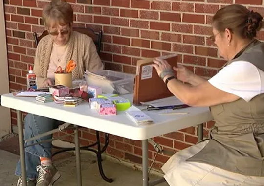 Two women make Soul Boxes at small table