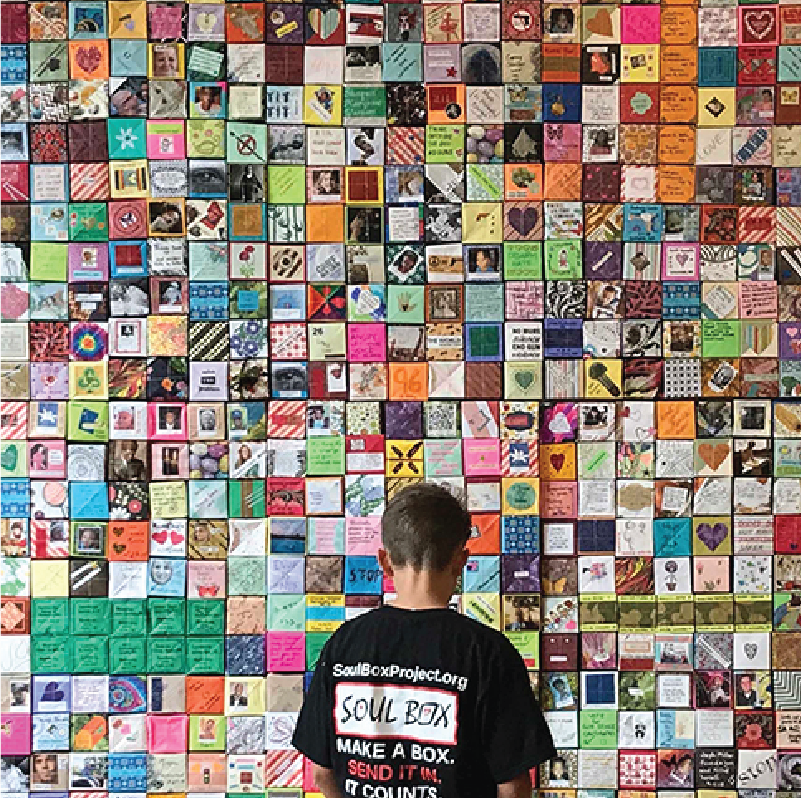 Boy examines wall of Soul Boxes, Institute for Loss and Transition, Portland, OR