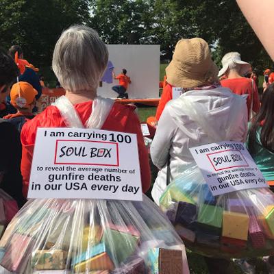 Marchers wear Soul Box backpacks at Wear Orange event