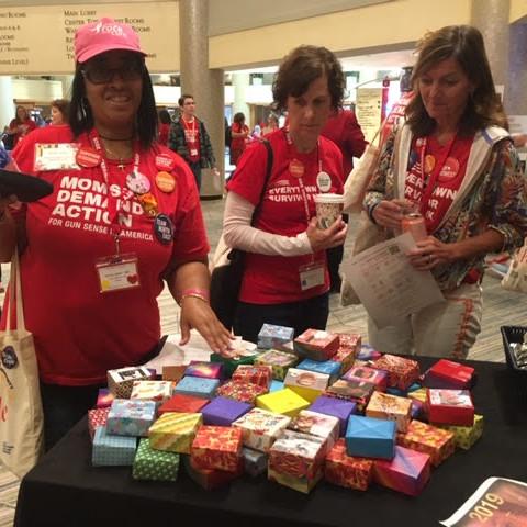Three women in Everytown T-shirts stop at Soul Box table, Gun Sense University, Washington, D.C.