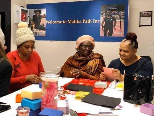 Three women with the Malik's Path organization fold Soul Boxes
