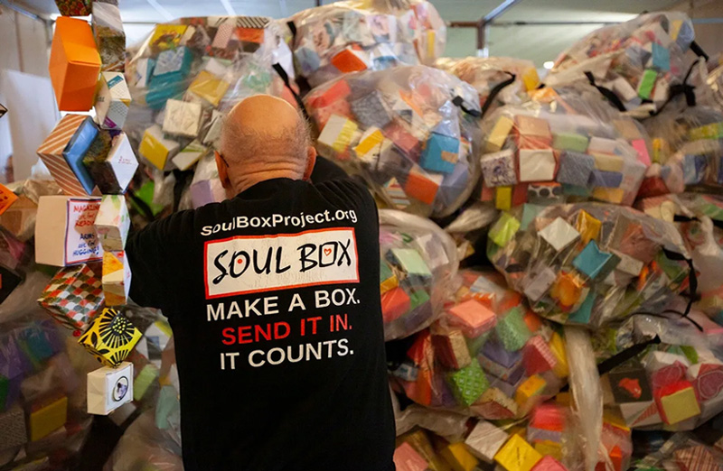 Soul Box Volunteer Holding up Pile of Bagged Boxes at State Capitol