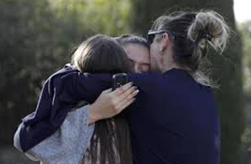 Mom hugging kids after gun violence at a school